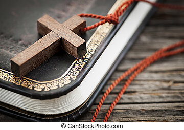 Cross on Bible - Closeup of simple wooden Christian cross...