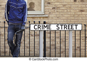 Burglar standing on street with crowbar and leather gloves...