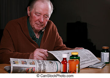 Elderly man reading newspaper at night - Elderly man reading...