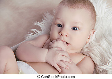 Close-up of Portrait funny baby lick his fingers of hand