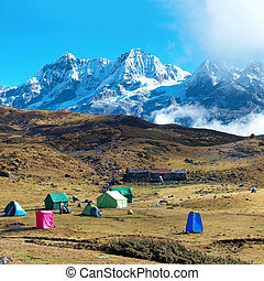 Campsite with tents on the top of high mountains, covered by...