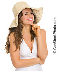 Happy young woman in swimsuit and hat looking on copy space