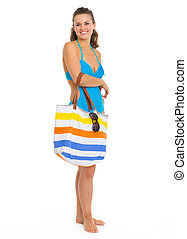 Full length portrait of smiling young woman in swimsuit with...