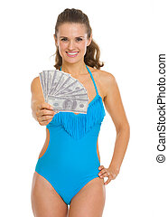 Smiling young woman in swimsuit showing fan of dollars