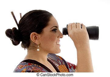 side pose of female watching through binocular against white...