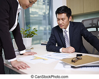 asian business people reviewing sales performance in office.