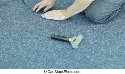 Worker spreading carpet. Lays carpet and smooth it with a...