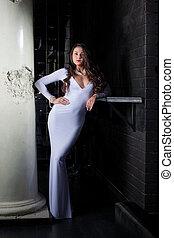 Luxurious brunette posing in elegant white dress