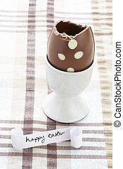 Happy easter message with half eaten chocolate egg on brown...