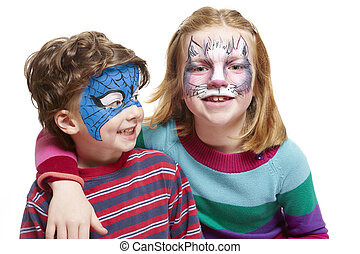 Young boy and girl with face painting of cat and superhero...
