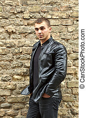 brutal young sexual man in a leather jacket - Closeup...