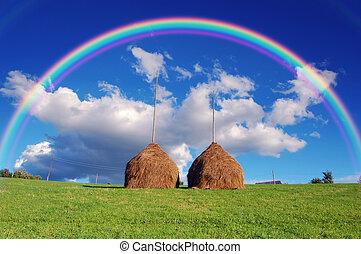 Rainbow over the haystacks - Summer mountain village...