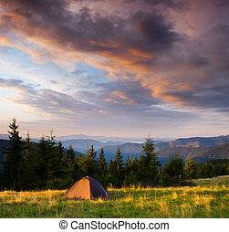 Sunrise in the mountains with a tent - Morning landscape in...