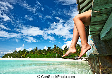 Woman at beach jetty - Woman's legs at beach jetty