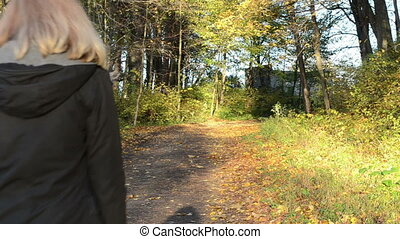 blond woman autumn road - blond woman walk on autumn park...