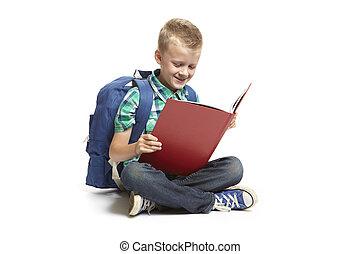School boy sitting reading - 8 year old school boy sitting...