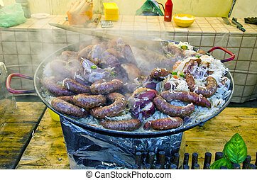 cooking sausages with vegetables in big pan