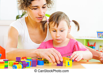 Young mother and little daughter playing with toy blocks