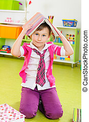 Cute little girl with book on head - Cute little girl making...