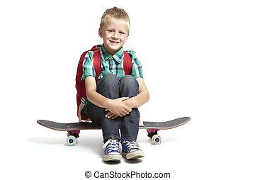 8 year old school boy with backpack sitting on a skateboard...