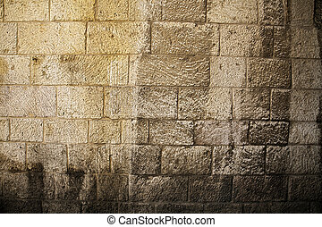 Sunlit Stone Wall Background - Rough textured yellow stone...