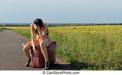 Despondent female hitchhiker in stilettoes and a sundress...