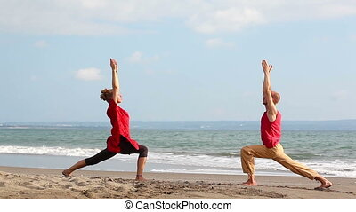 Pair yoga - Peaceful pair practicing yoga together on beach...