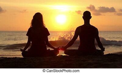 Pose lotus yoga - Couple sitting yoga on beach while sunset