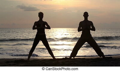Meditation - Couple doing exercise yoga on beach while...