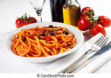 pasta with olives, bacon and sauce on the table with wine,...