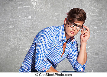 Fashion young man holding his glasses - Fashion young man...