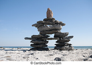 Inukshuk resting on the shoreline with blue sky copy space...