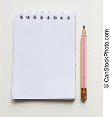 pencil and white paper note book on background