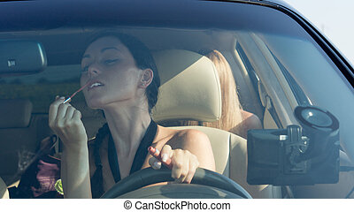 Woman driver applying lipstick using the rear view mirror in...