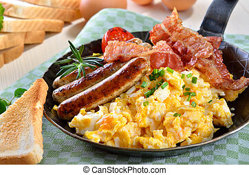 Scrambled eggs with fried bacon and hot sausages