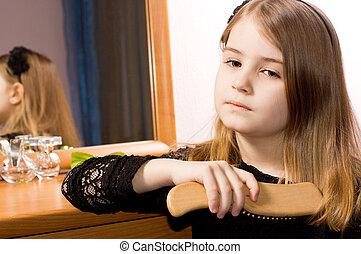 Sad little girl brushing her hair