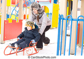 Mother pushing her son on a winter sled - Mother pushing her...