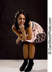 Beautiful young woman in a party dress posing in a crouched...