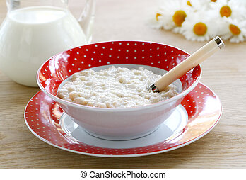 Porridge for breakfast in a red bowl on wooden table