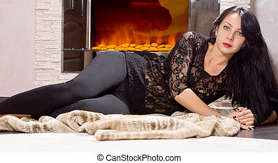 Glamorous woman lying in front of a fire - Glamorous young...