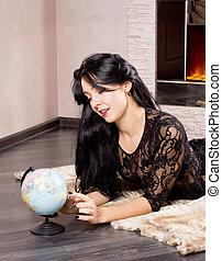 Beautiful woman playing with a globe - Beautiful woman lying...