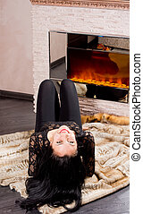 Playful beautiful woman lying on her back in front of a...