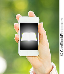 Smartphone with book in woman hand