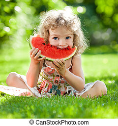 Child having picnic - Happy child with big red slice of...