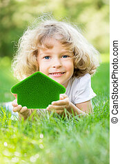 Happy child holding 3d house - Happy child holding green...