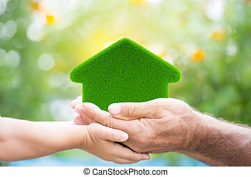 Eco-friendly house - Family holding grass house in hands...