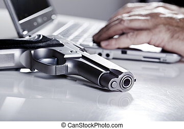 Computer Criminal - A 9mm handgun resting on a table, and...