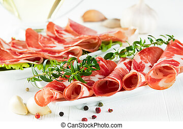 Thinly sliced ??ham on a narrow white plate.