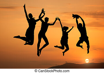 Silhouette of happy people jumping at sunset and sea