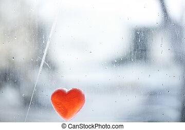 Rainy Heart - Heart shaped soap leaning on a window covered...